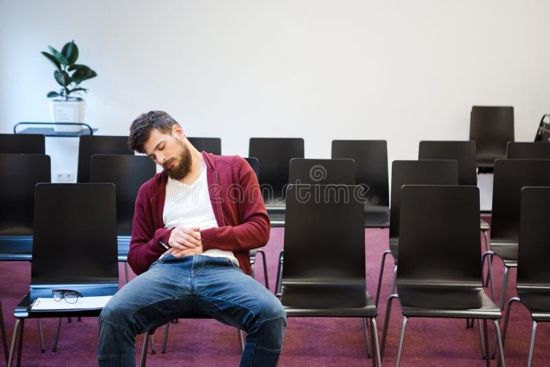 Бородатый парень сидя и спать в конференц-зале стоковые изображения