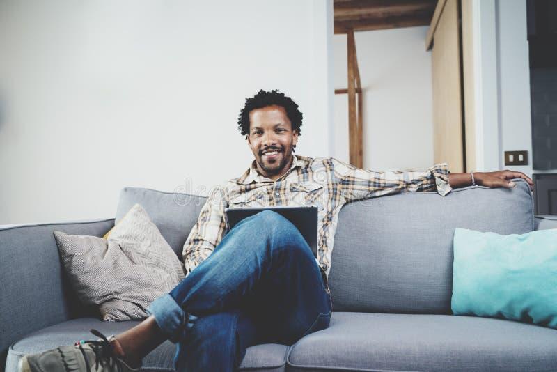 Бородатый усмехаясь американский африканский человек используя таблетку для видео- переговора пока ослабляющ на софе в современно стоковое изображение