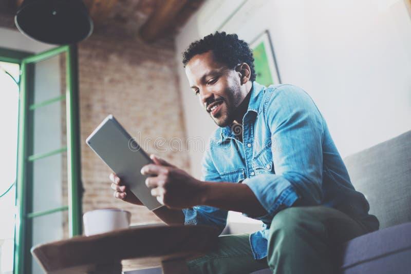 Бородатый усмехаясь африканский человек используя таблетку для видео- переговора пока ослабляющ на софе в современном офисе Конце стоковые фото