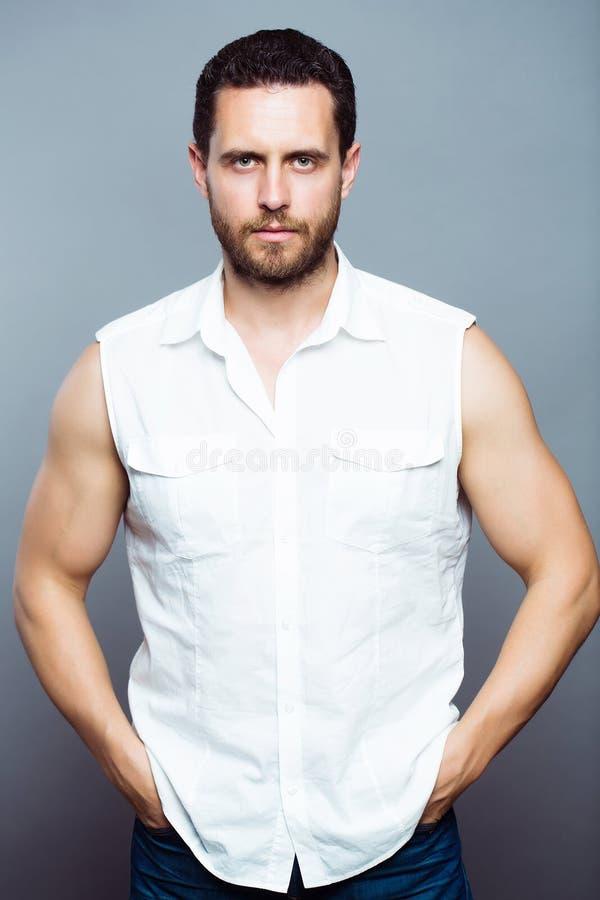 Бородатый человек в белой рубашке стоковые фото