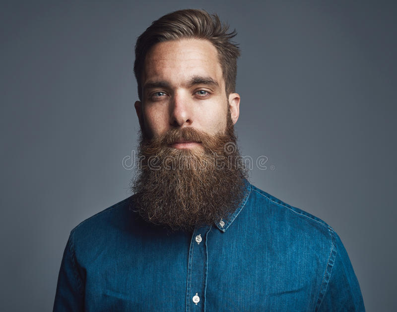 Бородатый человек в голубой джинсовой ткани с утомленным выражением стоковая фотография rf