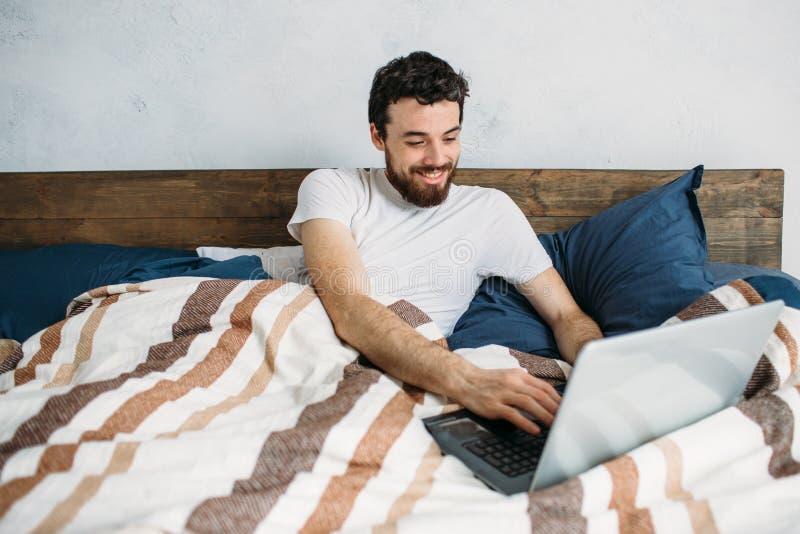 Бородатый человек лежа в кровати утра с компьтер-книжкой стоковые фотографии rf
