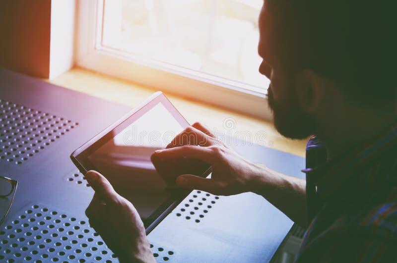 Бородатый человек держа цифровую таблетку стоковая фотография
