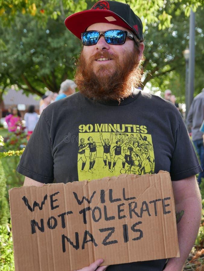 Бородатый человек держит ` мы не допустим знак ` нацистов стоковые фото