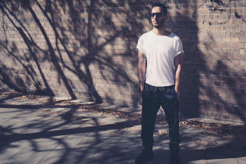 Бородатый человек при татуировка нося пустую белую футболку Стойки перед кирпичной стеной Предпосылка улицы города горизонтально стоковое изображение