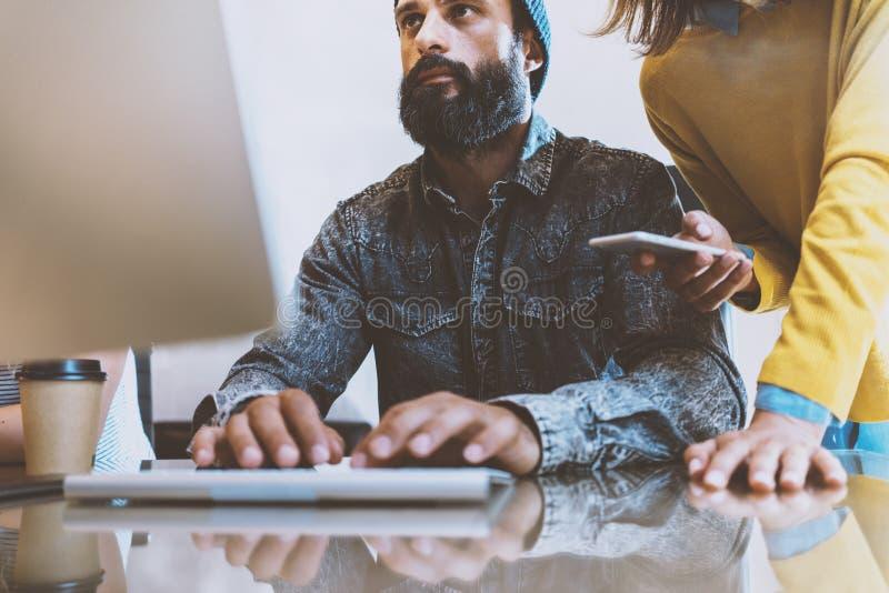 Бородатый человек работая в офисе Сотрудник печатая на клавиатуре компьютера Женщина стоя около его и держа smartphone стоковые изображения