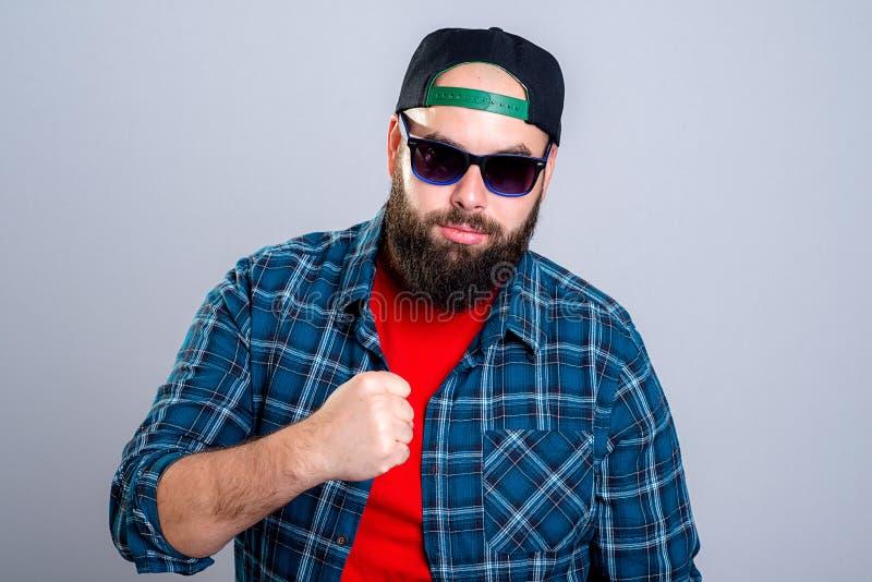 Бородатый человек с бейсбольной кепкой и солнечными очками смотрит сердитым стоковое фото rf