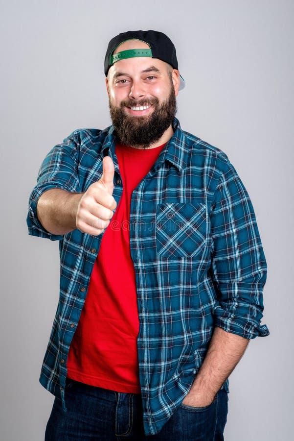 Бородатый человек с бейсбольной кепкой с большим пальцем руки вверх стоковые изображения rf