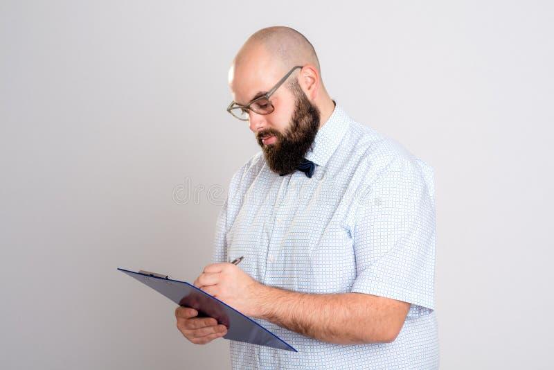 Бородатый человек с доской сзажимом для бумаги перед серой предпосылкой стоковая фотография