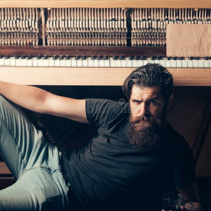 Бородатый человек с стеклянным близко деревянным роялем стоковые фотографии rf