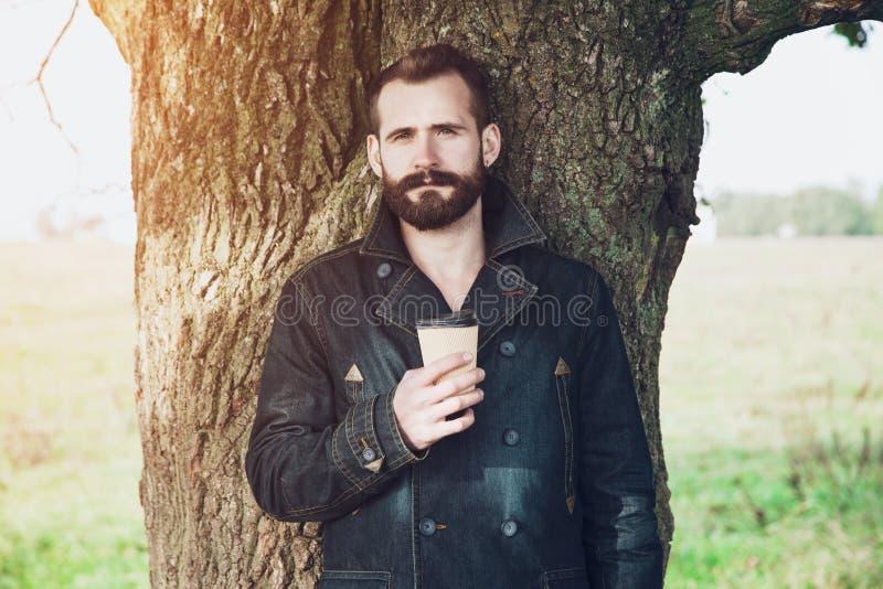 Бородатый человек с чашкой кофе в парке стоковая фотография