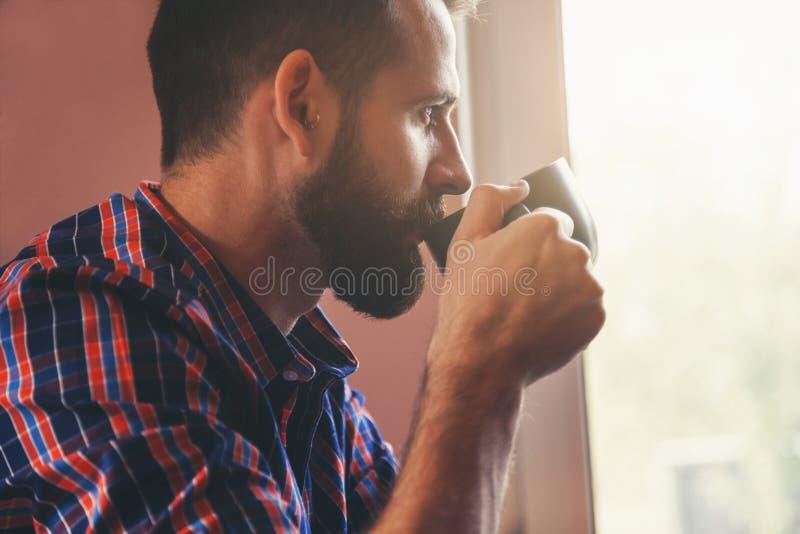 Бородатый человек с чашкой кофе утра стоковые фото