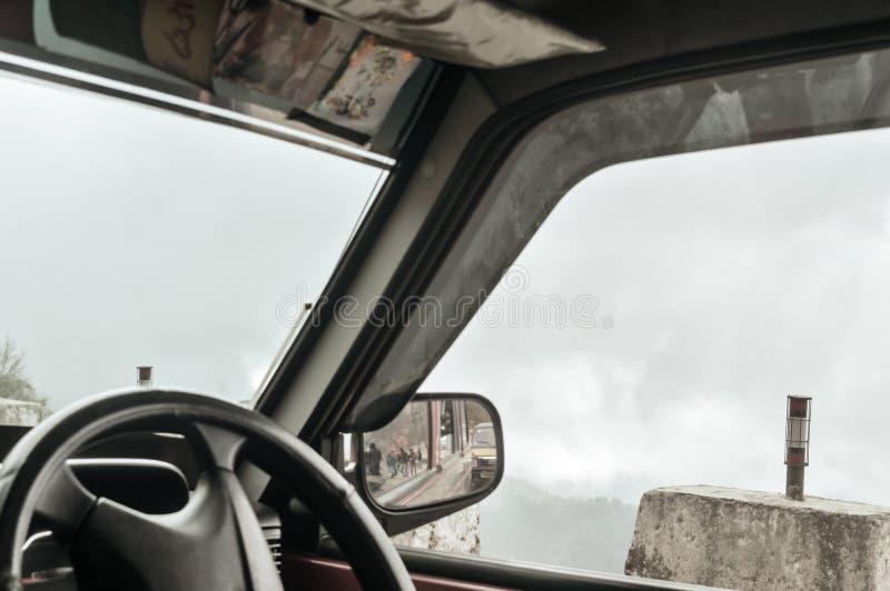Бортовое зеркало заднего вида на автомобиле на дороге сельской местности стоковая фотография