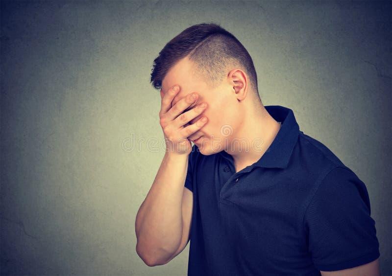 Бортовой профиль унылого человека с рукой над его стороной стоковое изображение