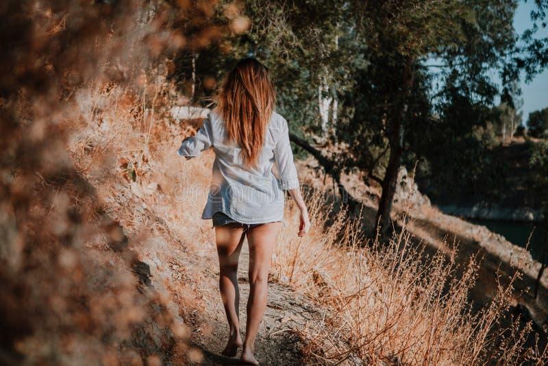 Босоногая женщина идя вдоль узкого пути в природе стоковая фотография