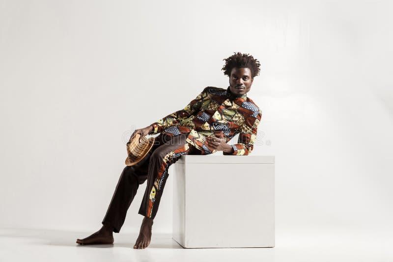 Босоногий африканский человек uncomfortble сидит на coub стоковые изображения