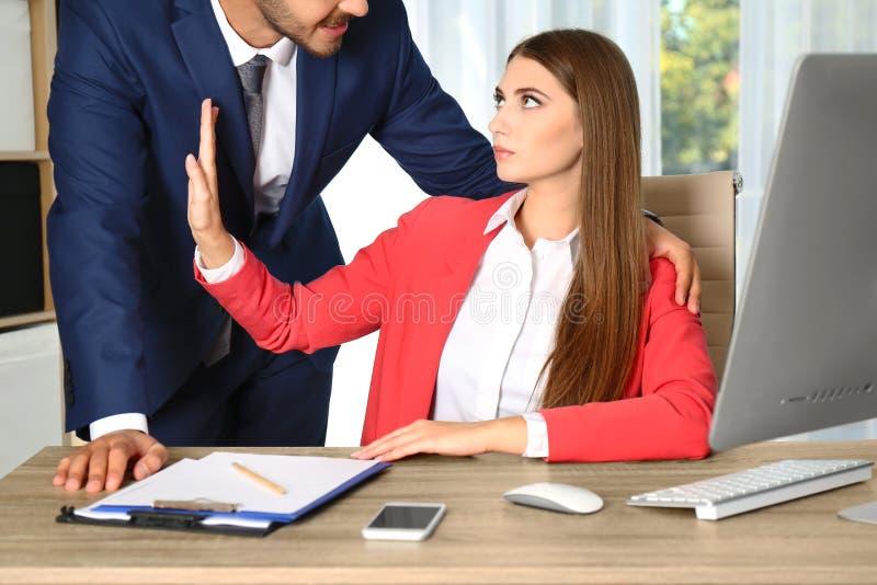Босс досаждая его женская секретарша в офисе стоковая фотография