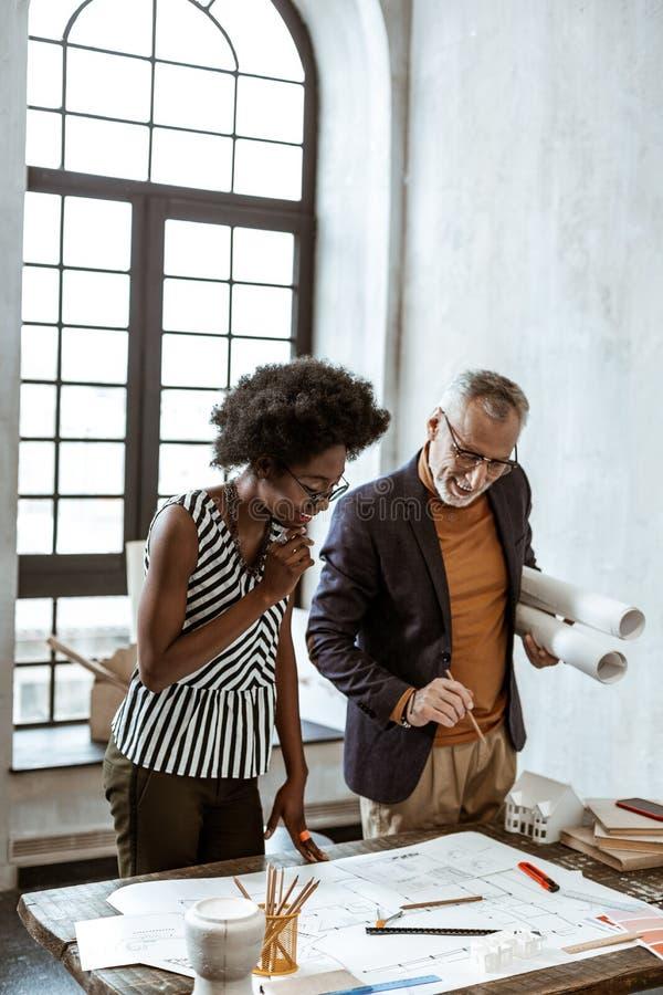 Босс компании дизайна интерьера помогая его работнику с задачей стоковое изображение