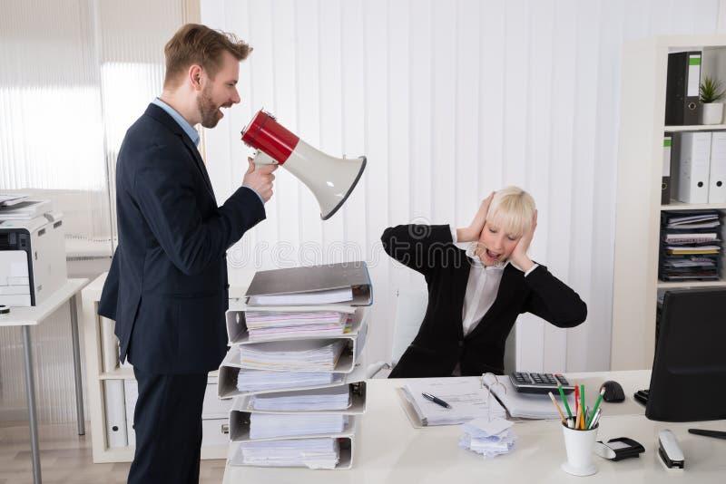 Босс крича на коммерсантке через громкоговоритель стоковое изображение