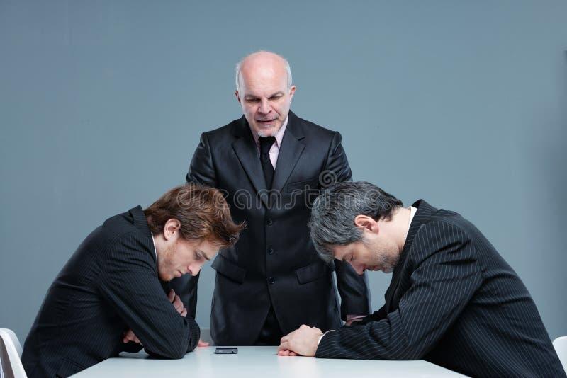 Босс одевая вниз 2 работников говоря им  стоковое фото rf