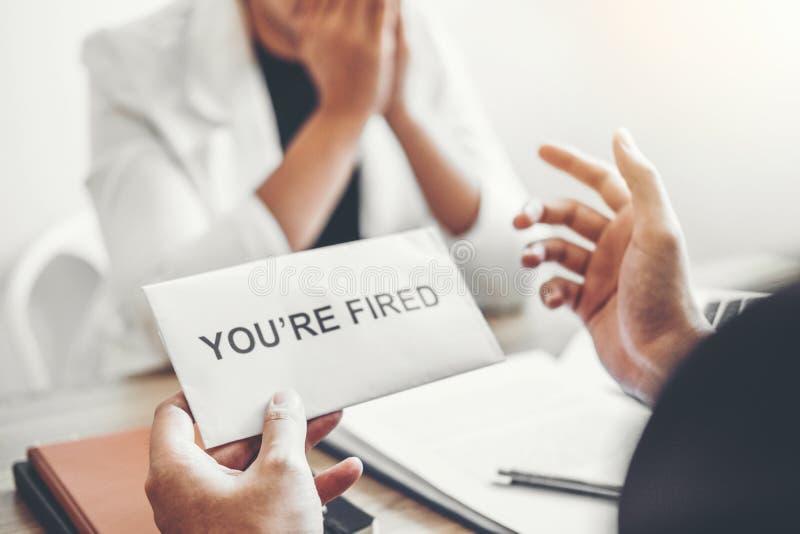 Босс отправляет уведомление об отставке в бизнес-леди усиливая для прекращенный работе пакуя коробку и выходя офис, безропотность стоковые фото