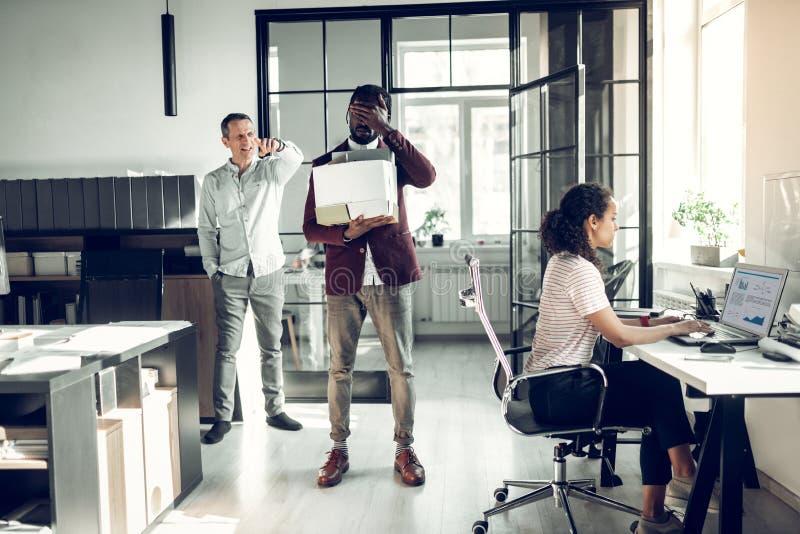 Босс увольняя неопытный ассистент от его офиса стоковые фотографии rf