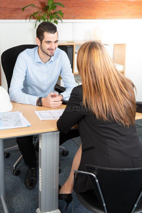 Босс человека красивый смотря менеджера маленькой девочки с улыбкой пока слушающ ее объяснения отчета стоковое изображение