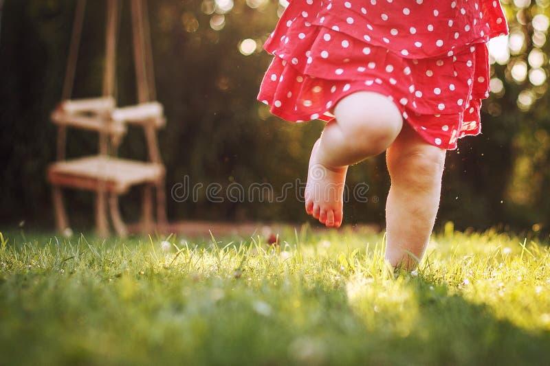 Босые ноги маленькой девочки в траве стоковое фото