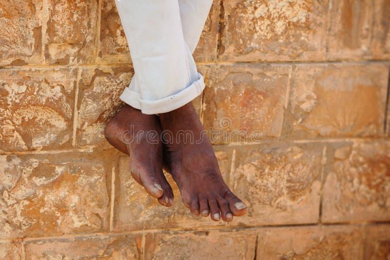 Босые ноги плохого индийского человека сидя на каменной стене Индия, Raj стоковые изображения