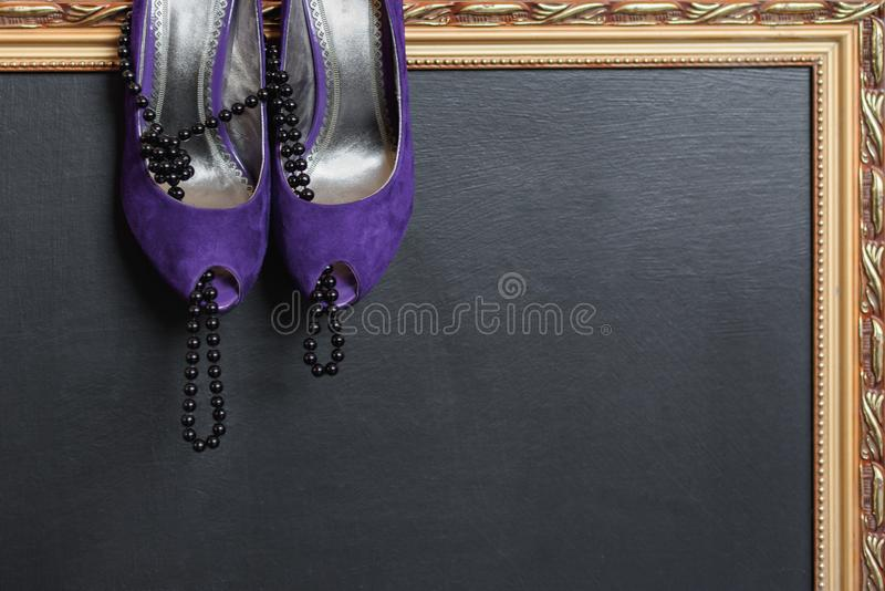 Ботинки бархата ` s женщин фиолетовые с высокими пятками и черными шариками принимают ботинки, на темной предпосылке с рамкой зол стоковое фото