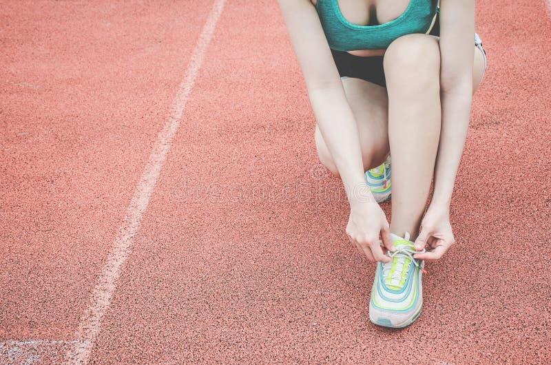 Ботинки бега - крупный план женщины связывая шнурки ботинка стоковые изображения