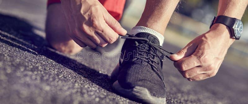 Ботинки бега - крупный план человека связывая шнурки ботинка стоковые изображения