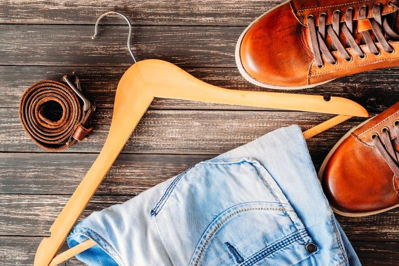 Ботинки Брайна кожаные вскользь, джинсы на поясе hangerand на деревянном взгляд сверху предпосылки женщина состава способа сторон стоковое изображение