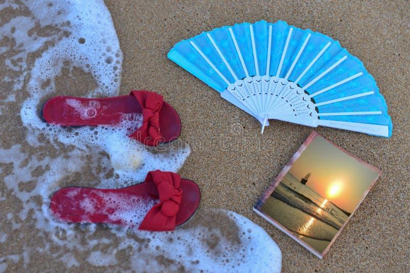 Ботинки вентилятор и книга на пляже стоковая фотография rf