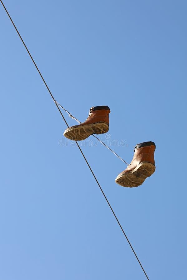 Ботинки вися на проводе над ясным голубым небом стоковое фото rf