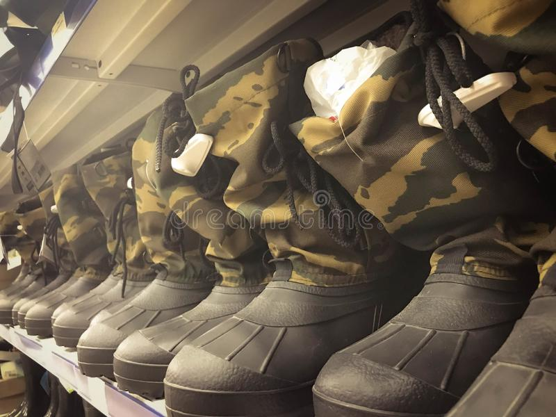 Ботинки военных резиновые, ботинки в toat защитных цветов хаки в ряд на полке в складе, магазине стоковое фото