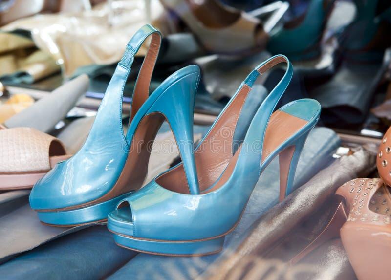 Ботинки голубых красивых женщин (отсутствие имени продукции) лежат среди другой обуви стоковое фото