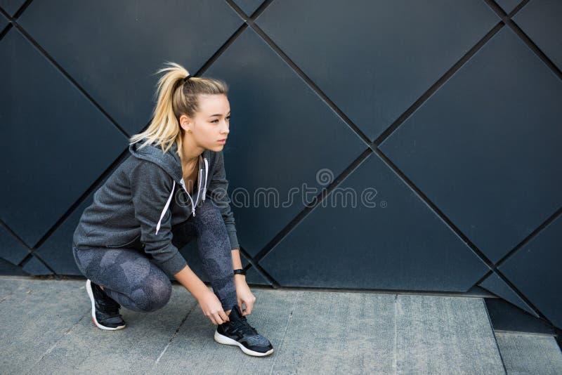 Ботинки женщины спортсмена пробуя идущие получая готовый для jogging outdoors в городе стоковые фотографии rf