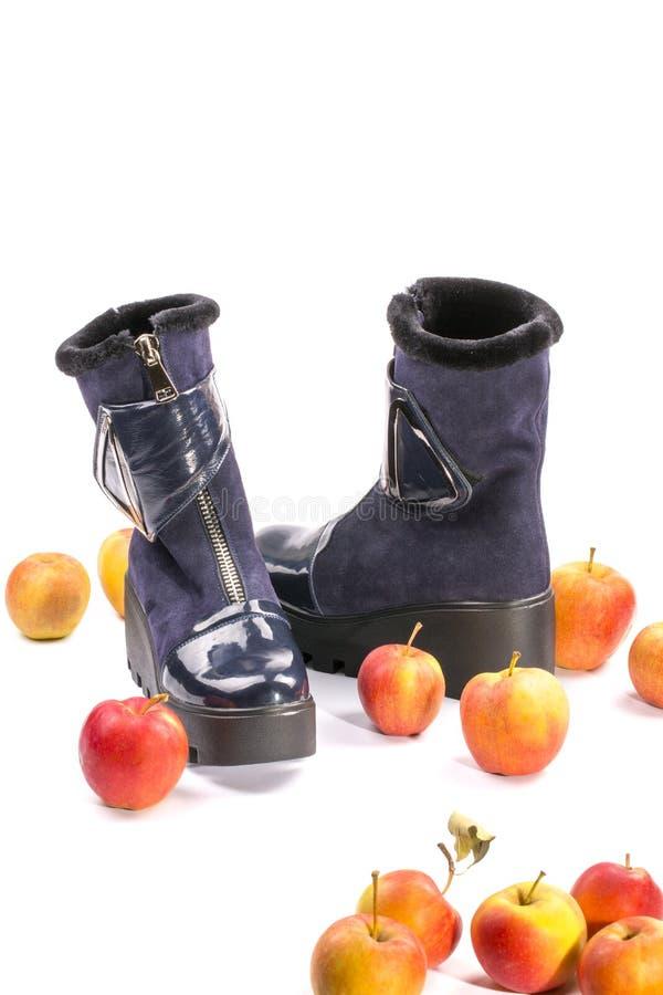 Ботинки зимы ` s женщин на высоких подошвах среди зрелых яблок стоковая фотография rf