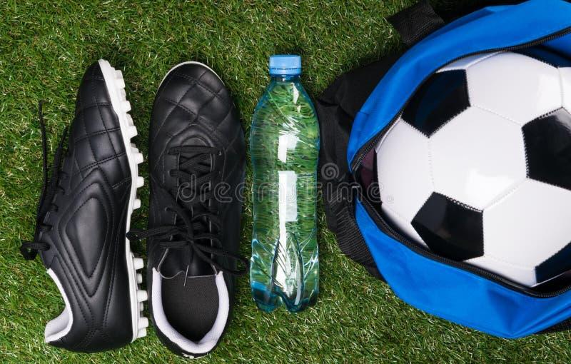 Ботинки и шарик для играть футбол на зеленой лужайке стоковое фото rf