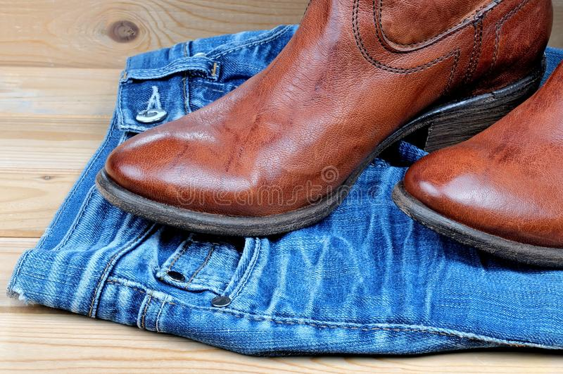 Ботинки ковбоя Брайна на голубых джинсах стоковые фотографии rf