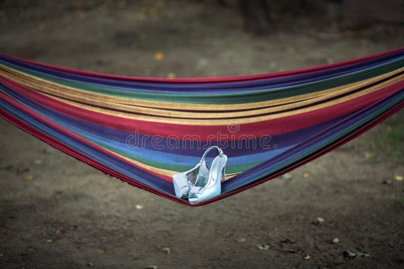 Ботинки свадьбы лежат на гамаке стоковые фотографии rf