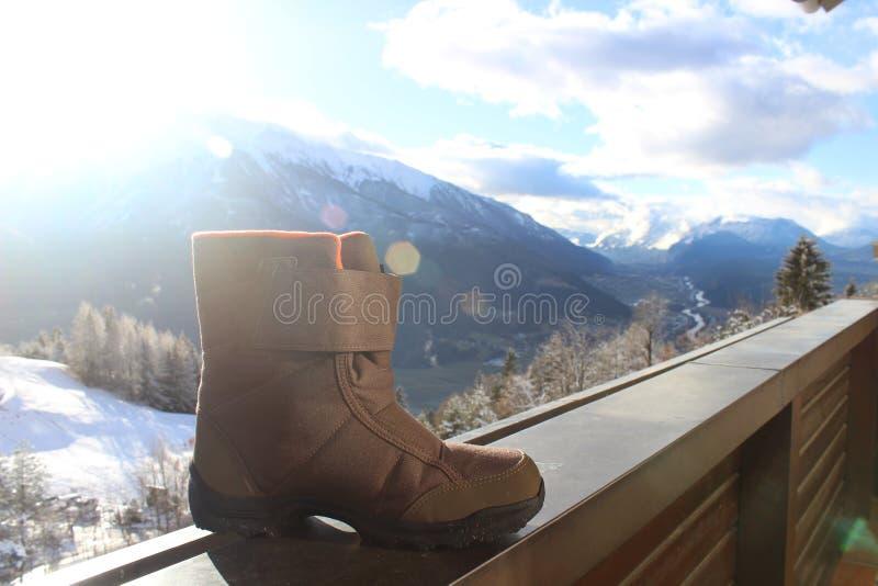 Ботинки снега на перилах с ландшафтом и солнечностью горы стоковая фотография rf