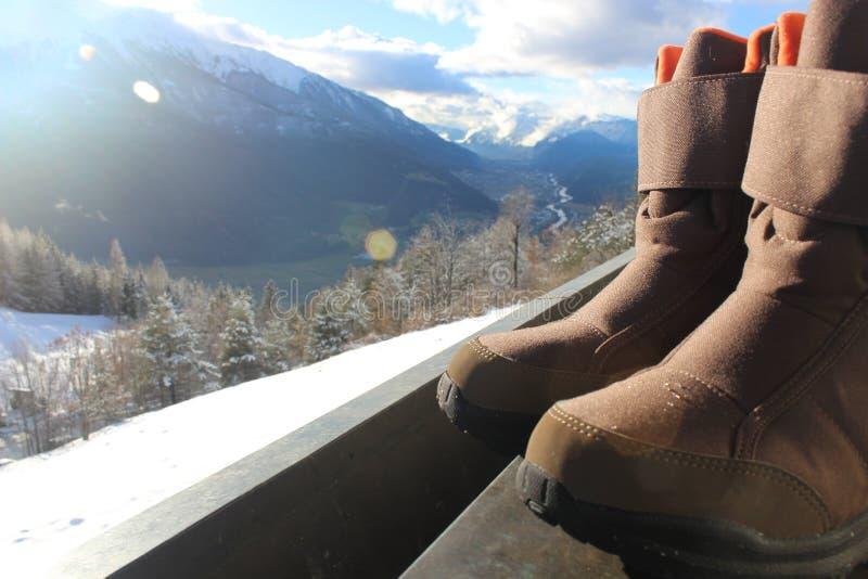 Ботинки снега на перилах с ландшафтом и солнечностью горы стоковое фото