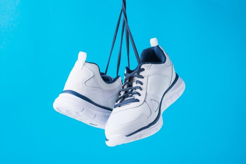 Ботинки спорта моды мужские на голубой предпосылке Стильные тапки человека для фитнеса, конца вверх стоковая фотография