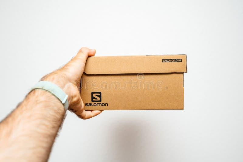 Ботинки спорта Salomon картонной коробки удерживания руки стоковые изображения rf