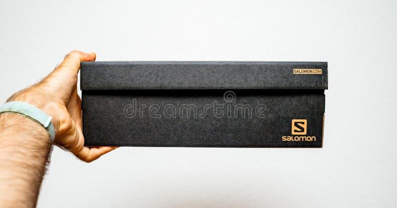 Ботинки спорта Salomon картонной коробки удерживания руки стоковые фотографии rf