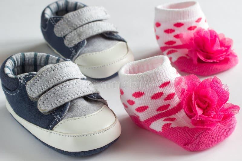 Ботинки для мальчика и розовые носки для девушек стоковое фото rf
