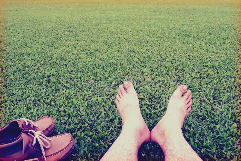 Ботинки ans ног людей на предпосылке сочной зеленой травы, винтажном стиле стоковое изображение rf