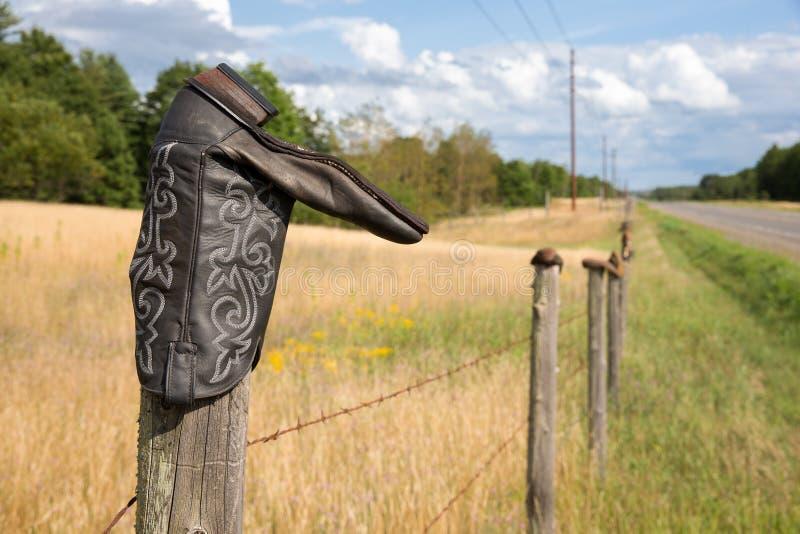 Ботинок ковбоя на столбе загородки стоковая фотография rf